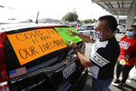 Disney employee Manuel Ortiz decorates his car with signs before a drive-by protest to demand a safe reopening amid the coronavirus pandemic Saturday, June 27, 2020, in Anaheim, Calif. Workers are demanding regular testing, stricter cleaning protocols and higher staffing levels. Disney had originally proposed reopening on July 17th but announced this week it was postponing. (AP Photo/Marcio Jose Sanchez)
