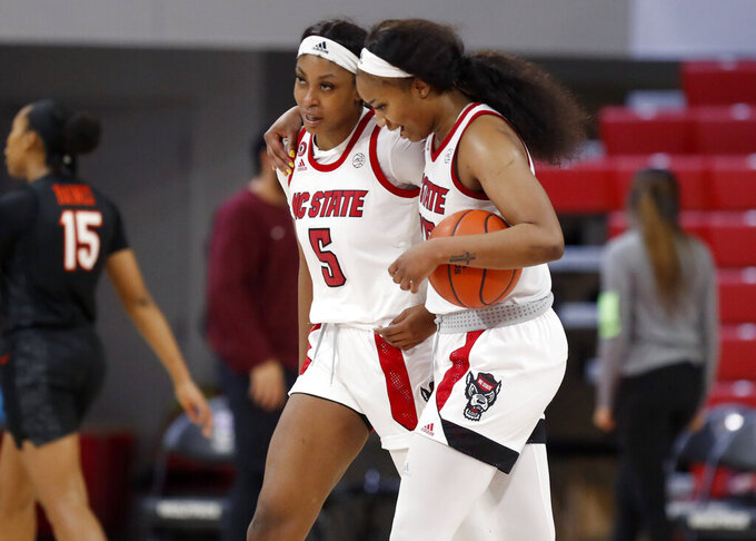 North Carolina State's Kayla Jones (25), right and Jada Boyd (5) walk off the court after an NCAA college basketball game against Virginia Tech, Sunday, Jan. 24, 2021 in Raleigh, N.C. (Ethan Hyman/The News & Observer via AP)