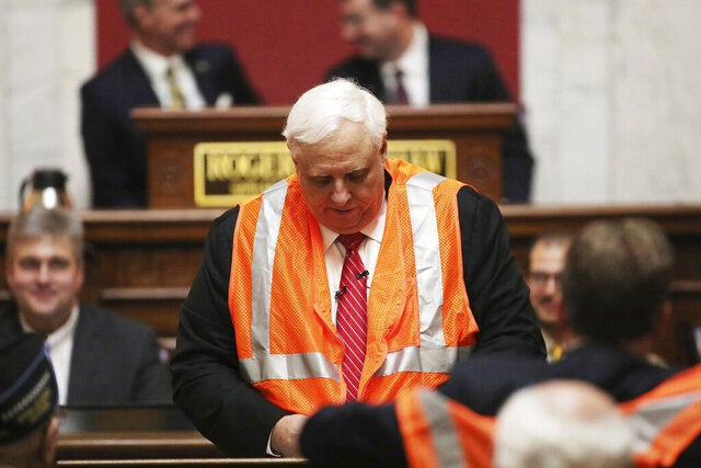 West Virginia Governor Jim Justice puts on a reflective vest during the State of the State address in the House Chambers at the state capitol, Wednesday, Jan. 8, 2020, in Charleston, W.Va. (AP Photo/Chris Jackson)