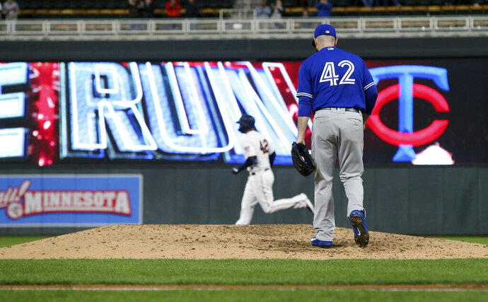 Toronto Blue Jays pitcher Matt Shoemaker, right, returns to the mound as Minnesota Twins' C.J. Cron rounds the bases on a three-run home run in the fourth inning of a baseball game Monday, April 15, 2019, in Minneapolis. (AP Photo/Jim Mone)