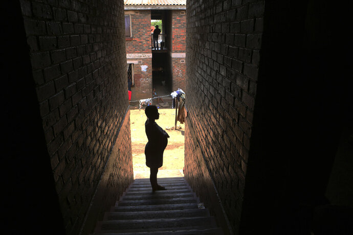 A pregnant woman waits in a passageway, waiting for her turn to deliver her baby, in a tiny apartment in the poor surburb of Mbare in Harare, Zimbabwe, in this Saturday, Nov. 16, 2019, with the help of 72-year old grandmother Esther Zinyoro Gwena. Grandmother Esther Zinyoro Gwena claims to be guided by the holy spirit and has become a local hero, as the country's economic crisis forces closure of medical facilities, and mothers-to-be seek out untrained birth attendants.(AP Photo/Tsvangirayi Mukwazhi)