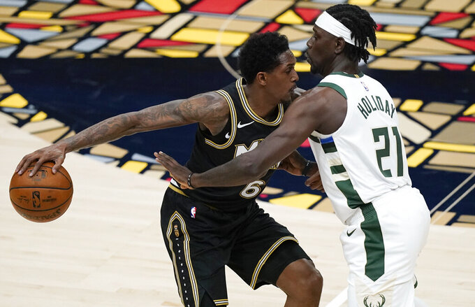Atlanta Hawks' Lou Williams (6) keeps the ball away from Milwaukee Bucks' Jrue Holiday (21) during the first half of Game 4 of the NBA basketball Eastern Conference finals Tuesday, June 29, 2021, in Atlanta. (AP Photo/Brynn Anderson)
