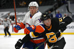 Boston Bruins' Curtis Lazar battles for position with New York Islanders' Anthony Beauvillier during the second period of an NHL hockey game Friday, April 16, 2021, in Boston. (AP Photo/Winslow Townson)