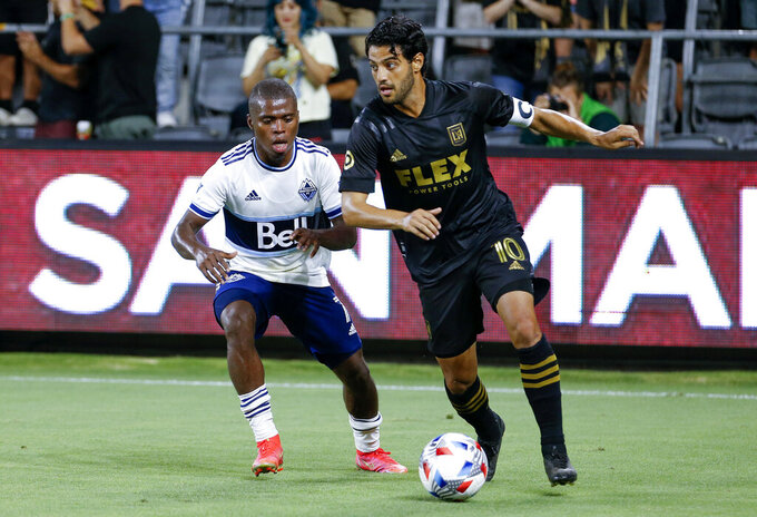 Los Angeles FC forward Carlos Vela (10) drives the ball past Vancouver Whitecaps midfielder Deiber Caicedo (7) during the second half of an MLS soccer match in Los Angeles, Saturday, July 24, 2021. The game ended in a 2-2 draw. (AP Photo/Ringo H.W. Chiu)