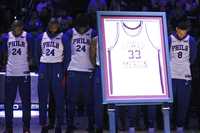 Philadelphia 76ers' Al Horford, from left, Kyle O'Quinn, Joel Embiid and Ben Simmons stand during a tribute for NBA basketball player Kobe Bryant before an NBA basketball game against the Golden State Warriors, Tuesday, Jan. 28, 2020, in Philadelphia. Bryant wore No. 33 while playing at Lower Merion High School. (AP Photo/Matt Slocum)