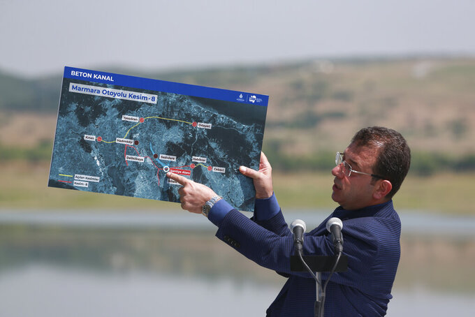 Ekrem Imamoglu, the mayor of Istanbul, points to a map as he talks during a media conference regarding the Kanal Istanbul project, near the construction site for the first bridge of the project on the edge of Sazlidere dam, in Istanbul, Thursday, June 24, 2021. Turkey's President Recep Tayyip Erdogan plans to build a controversial alternative waterway to the north of Istanbul that would bypass the Bosphorus Strait. Many, including Imamoglu, oppose the project fearing it would cause irreparable environmental damage. (AP Photo/Emrah Gurel)