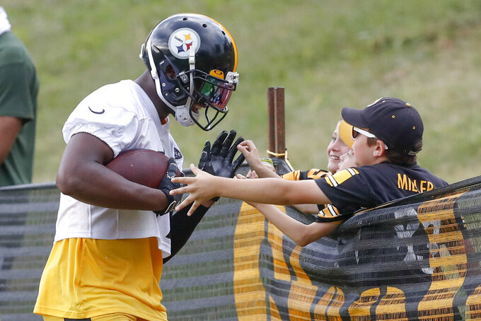 Pittsburgh Steelers wide receiver JuJu Smith-Schuster (19), left, talks with some young fans along the fence line after making a catch in drills during practice at NFL football training camp in Latrobe, Pa., Thursday, Aug. 15, 2019. (AP Photo/Keith Srakocic)