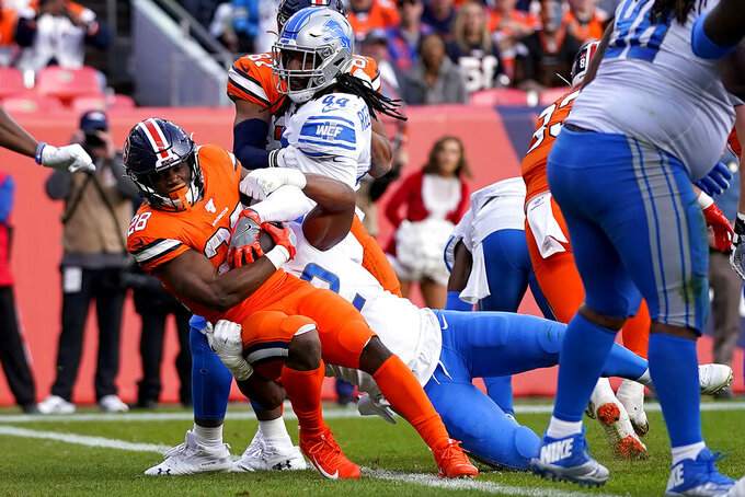 Denver Broncos running back Royce Freeman scores a touchdown as Detroit Lions outside linebacker Devon Kennard, right, defends during the first half of an NFL football game, Sunday, Dec. 22, 2019, in Denver. (AP Photo/Jack Dempsey)