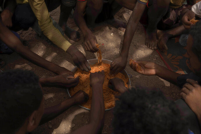 In this July 15, 2019 photo, Ethiopian migrants eat spaghetti as they take shelter under a tree, in Obock, Djibouti. The track through Djibouti ends on a long, virtually uninhabited coast outside the town of Obock, the shore closest to Yemen. Here migrants would stay, sometimes for several days, and wait for their turn on the boats that every night cross the narrow Bab el-Mandab straits to Yemen. (AP Photo/Nariman El-Mofty)