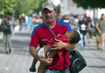 A Honduran migrant carries his son as he walks toward the U.S., in Chiquimula, Guatemala, Tuesday, Oct. 16, 2018. U.S. President Donald Trump threatened on Tuesday to cut aid to Honduras if it doesn't stop the impromptu caravan of migrants, but it remains unclear if governments in the region can summon the political will to physically halt the determined border-crossers. (AP Photo/Moises Castillo)