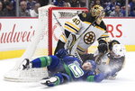Vancouver Canucks' Tyler Motte, bottom left, crashes into Boston Bruins goalie Tuukka Rask (40), of Finland, after being taken down by Patrice Bergeron during the first period of an NHL hockey game Saturday, Feb. 22, 2020, in Vancouver, British Columbia. (Darryl Dyck/The Canadian Press via AP)