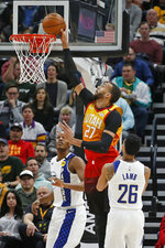 Utah Jazz center Rudy Gobert (27) dunks the ball as Indiana Pacers' Myles Turner, rear, and Jeremy Lamb (26) look on in the first half of an NBA basketball game Monday, Jan. 20, 2020, in Salt Lake City. (AP Photo/Rick Bowmer)