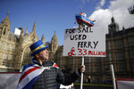 Steve Bray, a protestor who supports Britain remaining in the European Union and has been demonstrating across the street from the Houses of Parliament in London for more than 18 months, holds up a new placard he and other protestors made this morning, Tuesday, March 5, 2019. The U.K. government agreed Friday to pay 33 million pounds ($43 million) to settle a lawsuit that claimed it improperly awarded contracts to run extra ferry services in the event that Britain leaves the European Union without an agreement on future relations. (AP Photo/Matt Dunham)