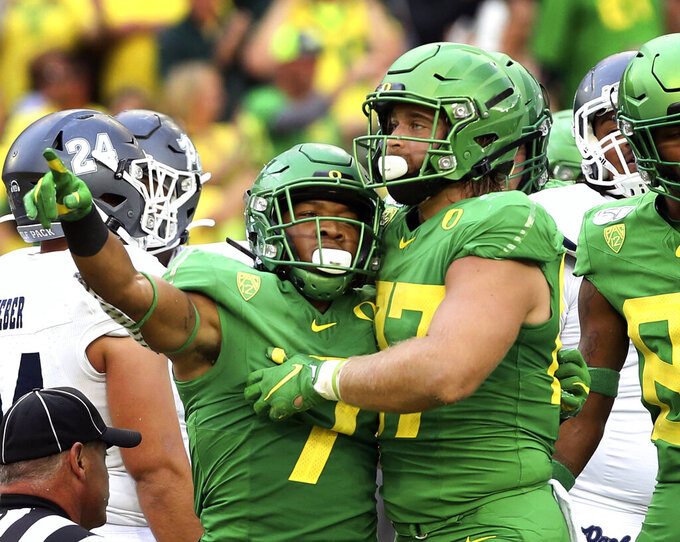 Oregon's CJ Verdell, left, and Ryan Bay, right, celebrate a touchdown during the second quarter of an NCAA college football game against Nevada Saturday, Sept. 7, 2019, in Eugene, Ore. (AP Photo/Chris Pietsch)