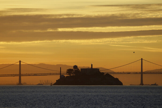 In this photo taken Feb. 1, 2018, Alcatraz Island is seen at sunrise on San Francisco Bay in this view from Sausalito, Calif. In the background is the San Francisco-Oakland Bay Bridge. The week of Nov. 18, 2019, marks 50 years since the beginning of a months-long Native American occupation at Alcatraz Island in the San Francisco Bay. The demonstration by dozens of tribal members had lasting effects for tribes, raising awareness of life on and off reservations, galvanizing activists and spurring a shift in federal policy toward self-determination. (AP Photo/Eric Risberg)