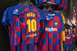 Lionel Messi shirts are displayed in a souvenir store in downtown Madrid, Spain, Friday, Aug. 6, 2021. Messi is leaving after leading Barcelona into its most glorious years. He helped the club win 35 titles, including the Champions League four times, the Spanish league 10 times, the Copa del Rey seven times and the Spanish Super Cup eight times. (AP Photo/Andrea Comas)