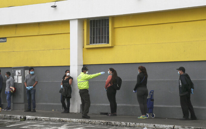 A police officer instructs shoppers to maintain a social distance as a precaution against the spread of the new coronavirus, as they wait in line to enter a supermarket in Quito, Ecuador, Saturday, March 28, 2020. The government has declared a health emergency, enacting a curfew and restricting movement to only those who provide basic services. (AP Photo/Dolores Ochoa)