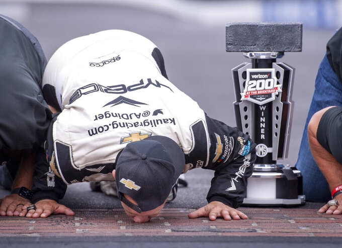 """AJ Allmendinger (16) kisses the """"yard of bricks"""" after winning a NASCAR Cup Series auto race at Indianapolis Motor Speedway, Sunday, Aug. 15, 2021, in Indianapolis. (AP Photo/Doug McSchooler)"""