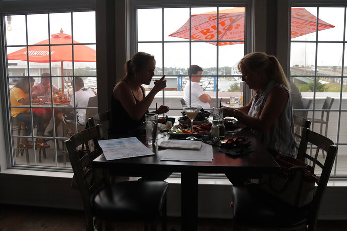 Two women eat lunch indoors at Portside Restaurant, Monday, June 22, 2020, in Salisbury, Mass. COVID-19 state guidelines allow indoor dining starting today. (AP Photo/Elise Amendola)