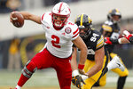 Nebraska quarterback Adrian Martinez (2) runs from Iowa defensive end A.J. Epenesa (94) during the first half of an NCAA college football game, Friday, Nov. 23, 2018, in Iowa City, Iowa. (AP Photo/Charlie Neibergall)