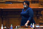 FILE - In this Monday, Dec. 14, 2020, file photo, Democrat Stacey Abrams walks on Senate floor before of members of Georgia's Electoral College cast their votes at the state Capitol in Atlanta. In a new interview with The Associated Press, voting rights advocate Abrams discussed a new state law that tightens some Georgia voting rules after Democrats carried the state in the 2020 elections. (AP Photo/John Bazemore, Pool, File)