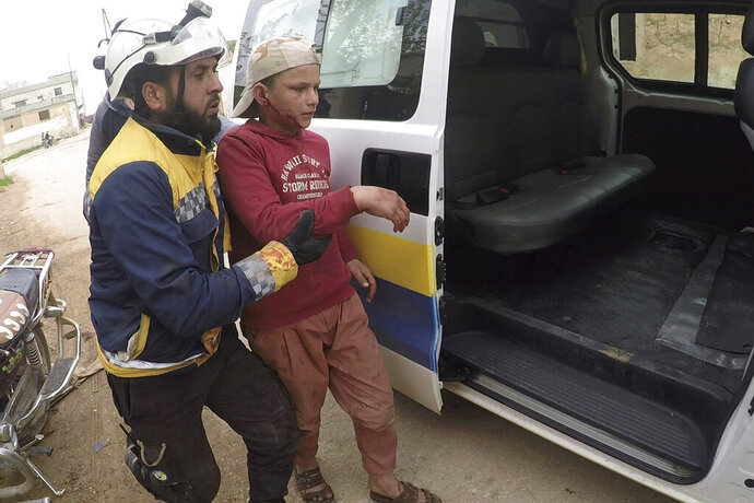This photo provided by the Syrian Civil Defense White Helmets, which has been authenticated based on its contents and other AP reporting, shows a civil defense worker helps a child after shelling at a street in Nairab town, in the eastern province of Idlib, Syria, Sunday, April 7, 2019. Opposition activists and Syrian state media are reporting at least 13 people have been killed in an exchange of violence between government forces and insurgents in the northwestern part of Syria. (Syrian Civil Defense White Helmets via AP)