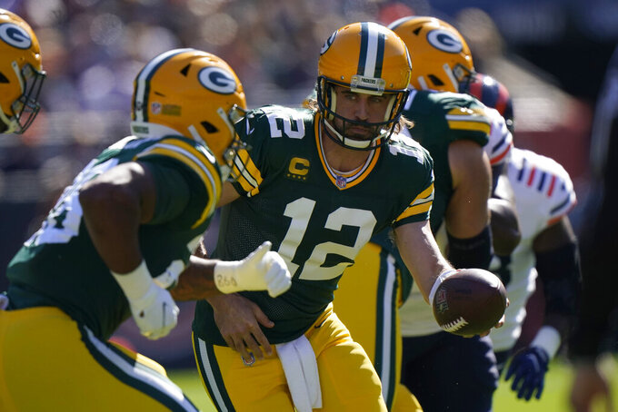 Green Bay Packers quarterback Aaron Rodgers (12) hands the ball off to running back A.J. Dillon during the first half of an NFL football game Sunday, Oct. 17, 2021, in Chicago. (AP Photo/Nam Y. Huh)