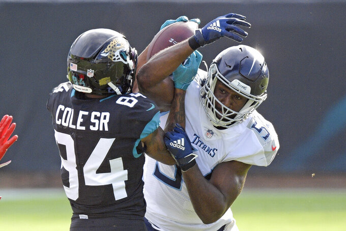 Tennessee Titans linebacker Rashaan Evans, right, breaks up a pass intended for Jacksonville Jaguars wide receiver Keelan Cole Sr. (84) during the first half of an NFL football game, Sunday, Dec. 13, 2020, in Jacksonville, Fla.(AP Photo/Phelan M. Ebenhack)