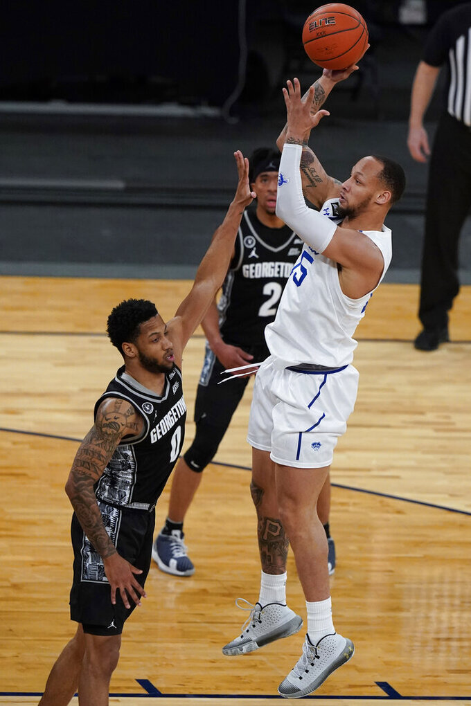 Seton Hall's Takal Molson, right, shoots over Georgetown's Jahvon Blair (0) during the second half of an NCAA college basketball game in the semifinals in the Big East men's tournament Friday, March 12, 2021, in New York. (AP Photo/Frank Franklin II)