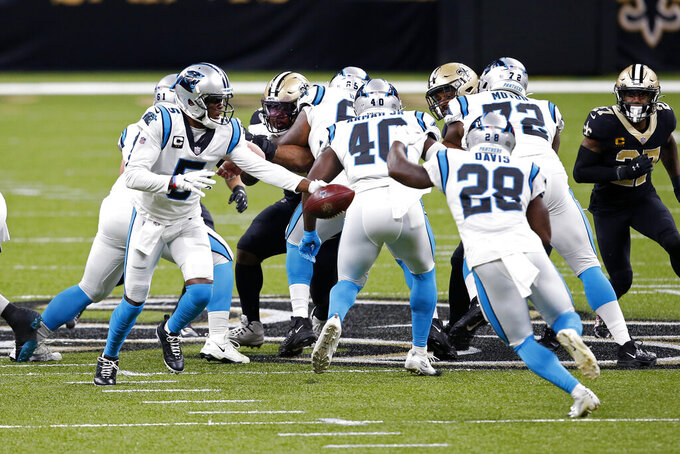 Carolina Panthers quarterback Teddy Bridgewater (5) hands off to running back Mike Davis (28) in the first half of an NFL football game against the Carolina Panthers in New Orleans, Sunday, Oct. 25, 2020. (AP Photo/Butch Dill)