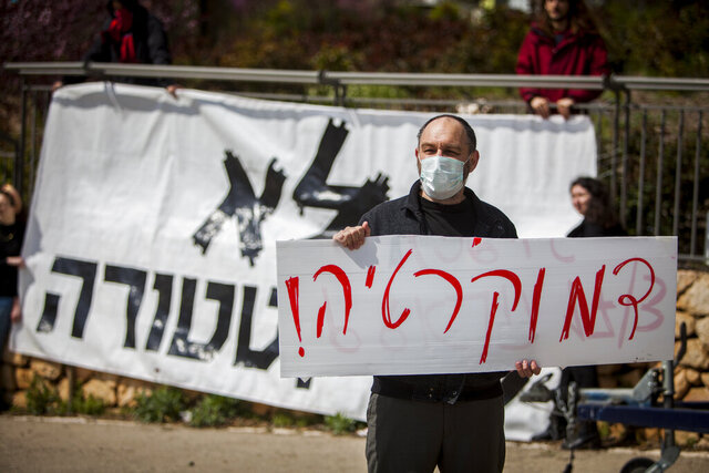 A man holds a sign that reads in Hebrew;