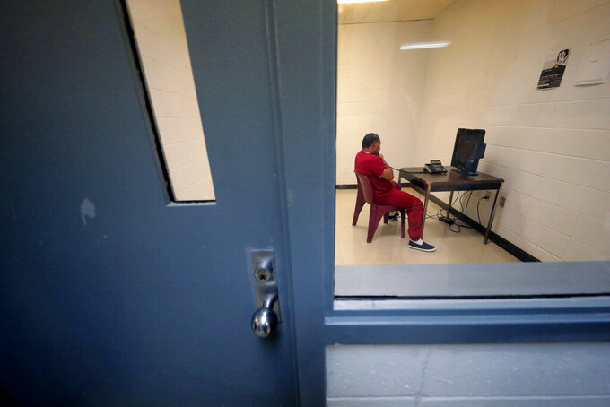 FILE — An immigration detainee sits in a room to use a telephone inside the Winn Correctional Center, in Winnfield, La., in this Sept. 26, 2019 file photo. The number of detainees nationwide has more than doubled since the end of February 2021, to nearly 27,000, according to recent data from U.S. Immigration and Customs Enforcement. (AP Photo/Gerald Herbert, File)
