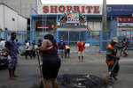 Volunteers sweep burnt out tyres on the roads in Lagos Saturday, Oct. 24, 2020. Nigeria's president says 51 civilians have been killed in unrest following days of peaceful protests over police abuses, and he blames