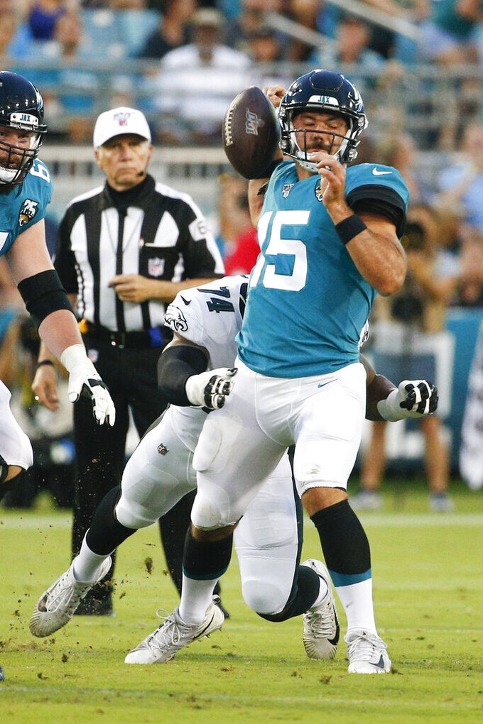 Jacksonville Jaguars quarterback Gardner Minshew (15) fumbles as he is hit by Philadelphia Eagles defensive end Daeshon Hall, left, during the first half of an NFL preseason football game, Thursday, Aug. 15, 2019, in Jacksonville, Fla. (AP Photo/Stephen B. Morton)