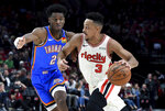 Portland Trail Blazers guard CJ McCollum, right, drives to the basket zx Oklahoma City Thunder guard Shai Gilgeous-Alexander defends during the second half of an NBA basketball game in Portland, Ore., Wednesday, Nov. 27, 2019. The Blazers won 136-119. (AP Photo/Steve Dykes)