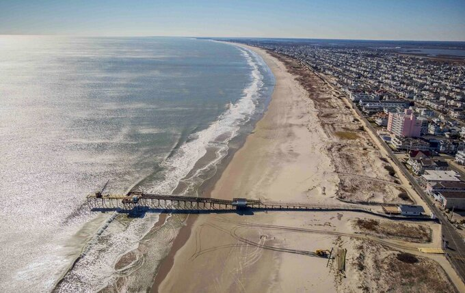 FILE - This Feb. 4, 2021, file photo shows the beach coastline of Ocean City, N.J. A large offshore wind energy project planned off the coast of New Jersey would run cables from the wind farm to potentially three locations, including Ocean City. (AP Photo/Ted Shaffrey, File)
