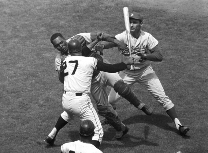 FILE - In this Aug. 22, 1965, file photo, San Francisco Giants pitcher Juan Marichal (27) swings a bat at Los Angeles Dodgers catcher John Roseboro as Dodgers pitcher Sandy Koufax, rear right, tries to break it up in the third inning at Candlestick Park in San Francisco. Violence is part of the game in many sports. But when the Cleveland's Myles Garrett ripped the helmet off Mason Rudolph and hit the Pittsburgh Steelers' quarterback in the head with it, the Browns' defender crossed a line _ one that attracts the attention of authorities sometimes from within their sport and in other cases from criminal prosecutors. (AP Photo/Robert H. Houston, File)