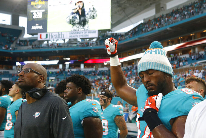 "FILE - In this Aug. 9, 2018, file photo, Miami Dolphins defensive end Robert Quinn (94) raises his right fist during the singing of the national anthem, before the team's NFL preseason football game against the Tampa Bay Buccaneers, in Miami Gardens, Fla. Dallas Cowboys defensive end Robert Quinn says the issue of protesting during the national anthem ""might come up"" before the season with owner Jerry Jones, who in the past has taken a hardline stance against displays by his players. Quinn joined the Cowboys in an offseason trade. (AP Photo/Wilfredo Lee, File)"