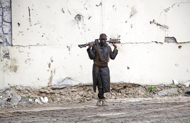 A Somali soldier stands at the scene of a suicide car bomb near the port in Mogadishu, Somalia Saturday, July 4, 2020. Explosions rocked two of Somalia's largest cities on Saturday as officials said a suicide car bomber detonated near the port in Mogadishu and a land mine was detonated by remote control as people were dining in a restaurant on the outskirts of Baidoa. (AP Photo/Farah Abdi Warsameh)
