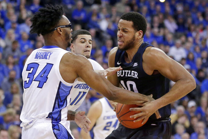 Creighton's Denzel Mahoney (34) and Marcus Zegarowski (11) take the ball away from Butler's Bryce Nze (10) during the first half of an NCAA college basketball game in Omaha, Neb., Sunday, Feb. 23, 2020. (AP Photo/Nati Harnik)