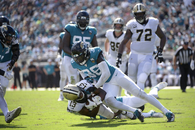 FILE - New Orleans Saints wide receiver Michael Thomas (13) is tackled by Jacksonville Jaguars cornerback A.J. Bouye (21) and defensive back Ronnie Harrison (36) after catching a pass during the second half of an NFL football game Sunday, Oct. 13, 2019, in Jacksonville, Fla. The Cleveland Browns have acquired safety Ronnie Harrison in a trade with the Jacksonville Jaguars, who will receive a fifth-round pick in 2021 from Cleveland. The loss of rookie safety Grant Delpit for the season with a torn Achilles tendon sent the Browns shopping for a safety. On Thursday, Sept. 3, 2020, general manager Andrew Berry pulled off the swap for Harrison, who is in his third season from Alabama. (AP Photo/Phelan M. Ebenhack, File)