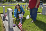 Connie Groblebe places lilacs at the grave of her in-laws, Frank and Helen Groblebe at the Mountview Cemetery on Memorial Day,  in Billings, Mont., Monday, May 25, 2020. Groblebe says that with the annual Memorial Day ceremony at the cemetery curtailed by the coronavirus, it was quiet and