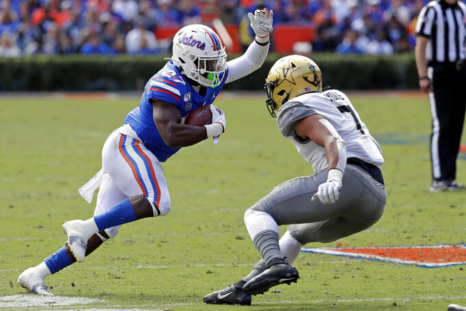 Florida running back Dameon Pierce, left, runs for yardage against Vanderbilt linebacker Dimitri Moore (7) during the first half of an NCAA college football game, Saturday, Nov. 9, 2019, in Gainesville, Fla. (AP Photo/John Raoux)