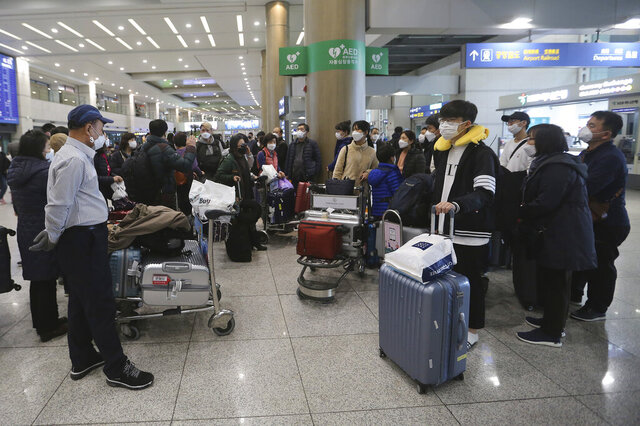 South Koreans tourists gather after returning from Israel at Incheon International Airport in Incheon, South Korea, Tuesday, Feb. 25, 2020. South Korean tourists returned home from Israel on Tuesday after the Israeli government imposed entry ban on South Koreans over concerns about new coronavirus. (AP Photo/Ahn Young-joon)
