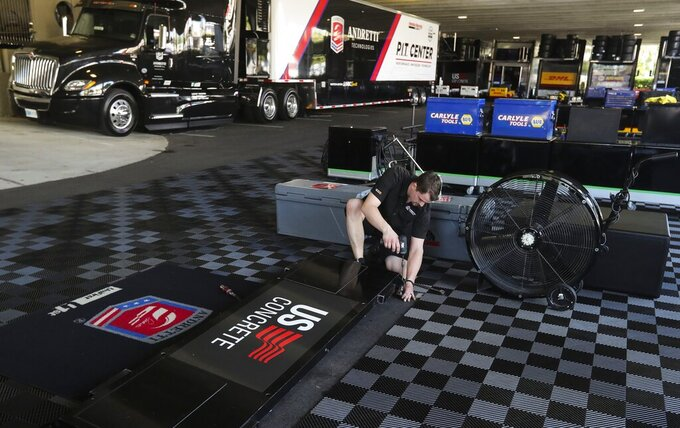 Kirby What, the front end mechanic for driver Marco Andretti, works to pack up the paddock area at the IndyCar Grand Prix of St. Petersburg, Friday, March 13, 2020 in St. Petersburg. NASCAR and IndyCar have postponed their weekend schedules at Atlanta Motor Speedway and St. Petersburg, due to concerns over the COVID-19 pandemic. (Dirk Shadd/Tampa Bay Times via AP)
