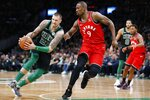 Toronto Raptors' Serge Ibaka (9) defends against Boston Celtics' Daniel Theis (27) during the first half on an NBA basketball game in Boston, Saturday, Dec. 28, 2019. (AP Photo/Michael Dwyer)