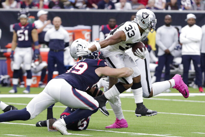Oakland Raiders running back DeAndre Washington (33) is hit by Houston Texans defensive end J.J. Watt (99) on a run during the first half of an NFL football game Sunday, Oct. 27, 2019, in Houston. (AP Photo/Michael Wyke)