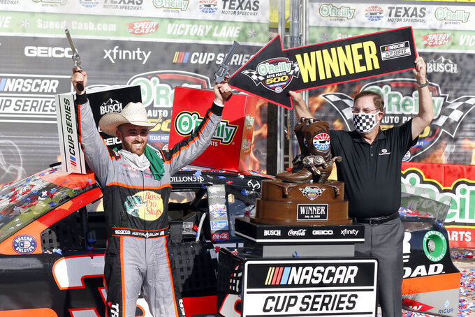 "Texas Motor Speedway President and General Manager Eddie Gossage, right, holds a ""winner"" sign as Austin Dillon, left, celebrates by firing six shooters after winning the NASCAR Cup Series auto race at Texas Motor Speedway in Fort Worth, Texas, Sunday, July 19, 2020. (AP Photo/Ray Carlin)"