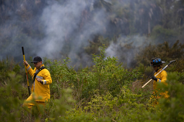 Miami-Dade firefighters Christian Blanco, left, and Matthew Gutierrez, put out spot fires, Thursday, May 14, 2020, off 26th Street in Golden Gate Estates, Fla. (Jon Austria/Naples Daily News via AP)