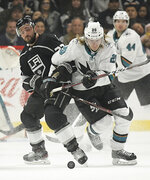 Los Angeles Kings defenseman Alec Martinez, left, and San Jose Sharks left wing Marcus Sorensen vie for the puck during the first period of an NHL hockey game Thursday, March 21, 2019, in Los Angeles. (AP Photo/Mark J. Terrill)